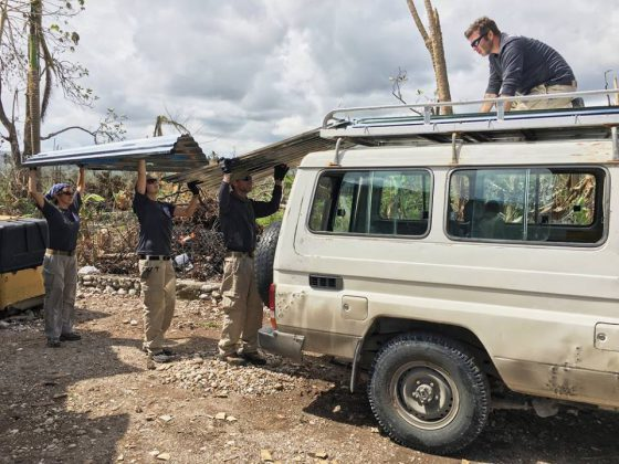 """Volunteers unload galvanized metal sheeting paid for in part by One Hundred for Haiti. Photo By Tom Hudson Day 1 of 30 in our series of photos called #onehundredforhaiti #hopeandsurvival""""  See them all on Facebook at http://tinyurl.com/HopeAndSurvival"""