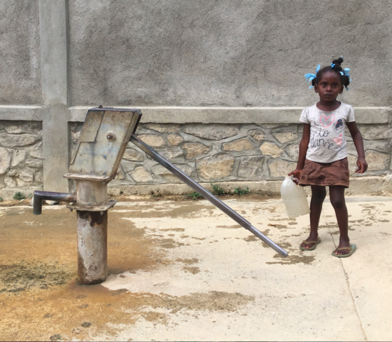 Little girl in Ranquitte Haiti pumping water